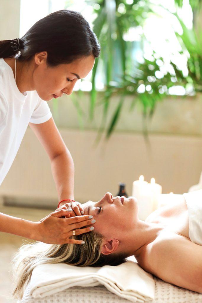 Asian masseuse massaging face of client