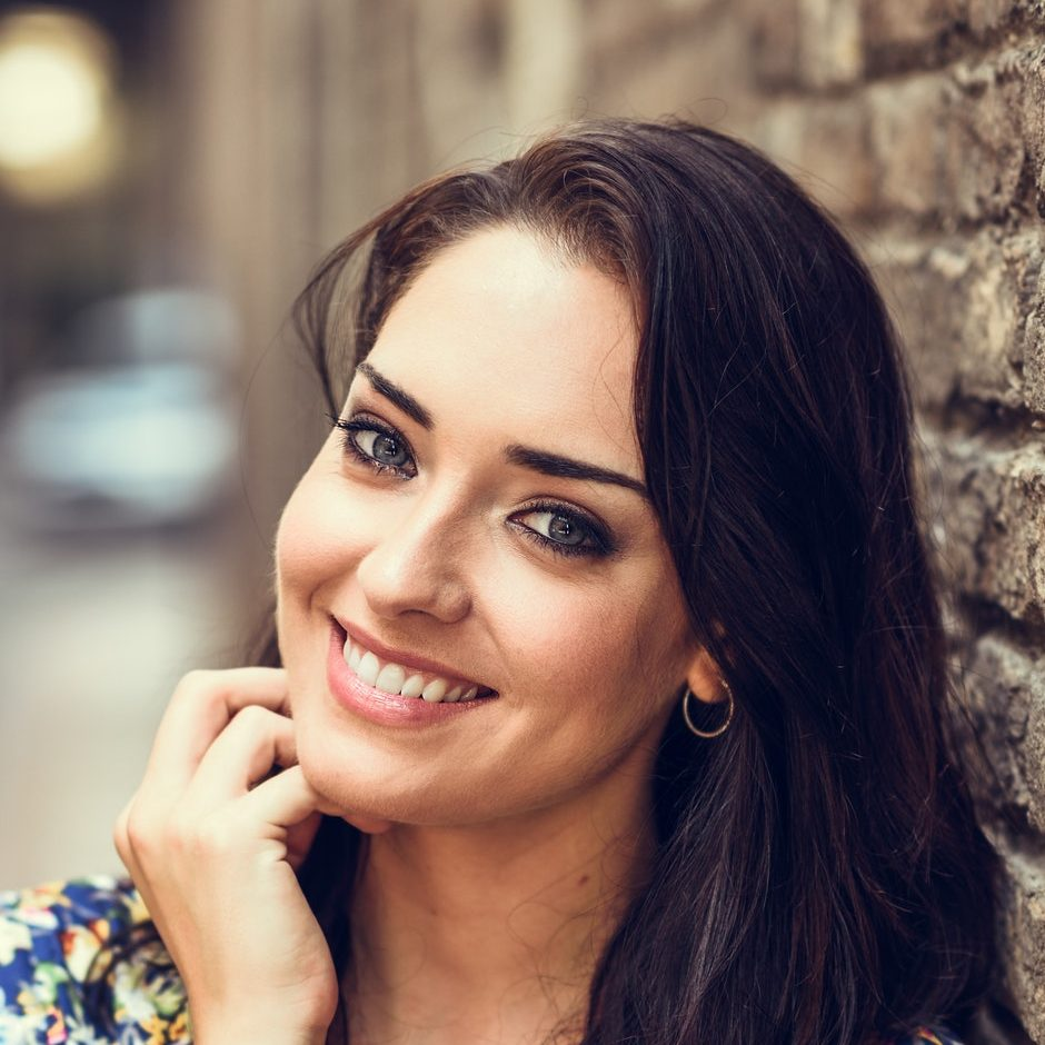 Girl with blue eyes smiling on brick wall.