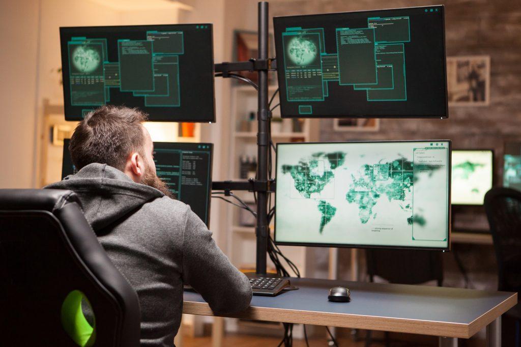 Rear view of dangerous hacker typing a malware