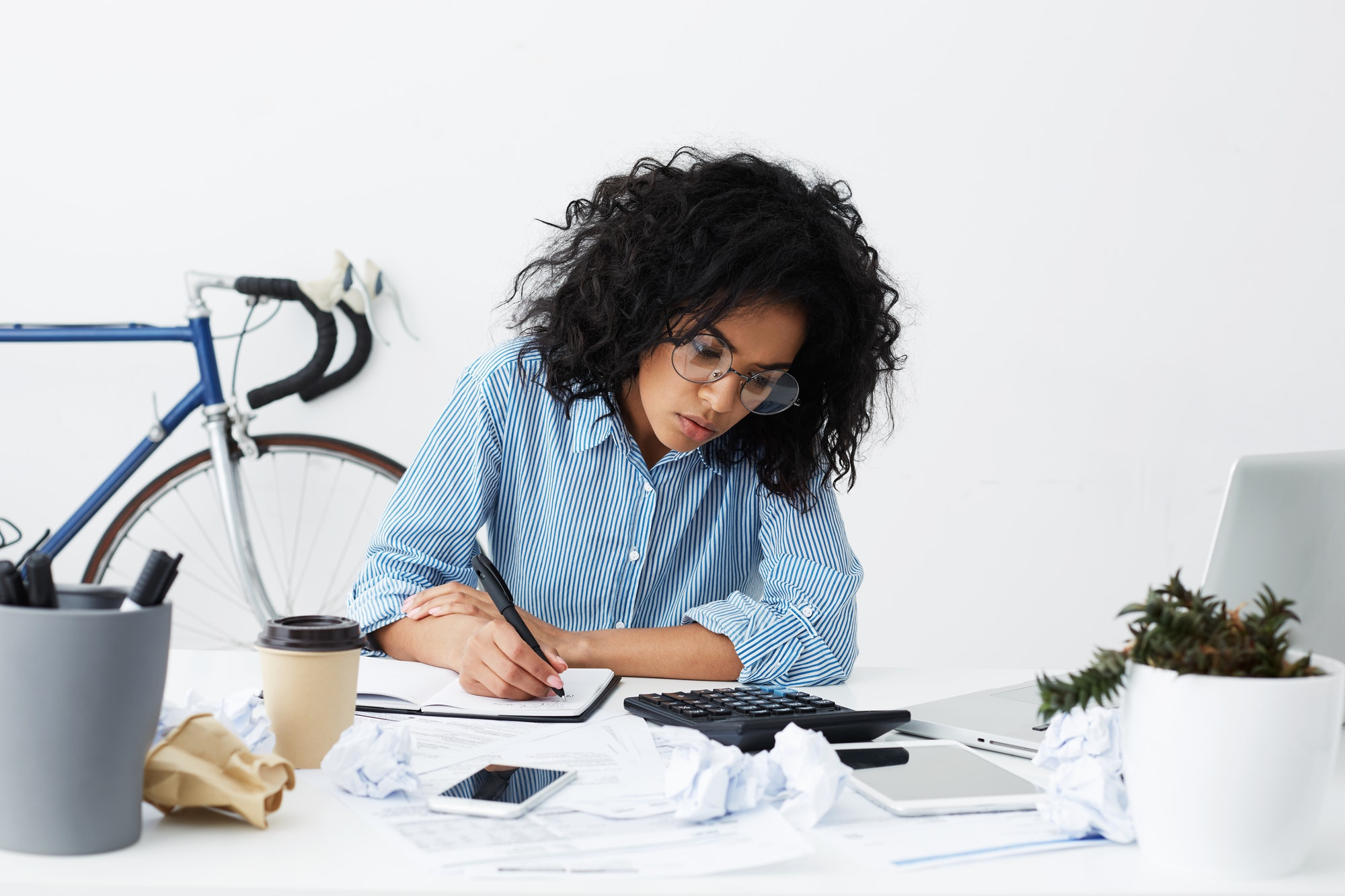 Attractive young dark-skinned female columnist suffering from writer's block, working on new article