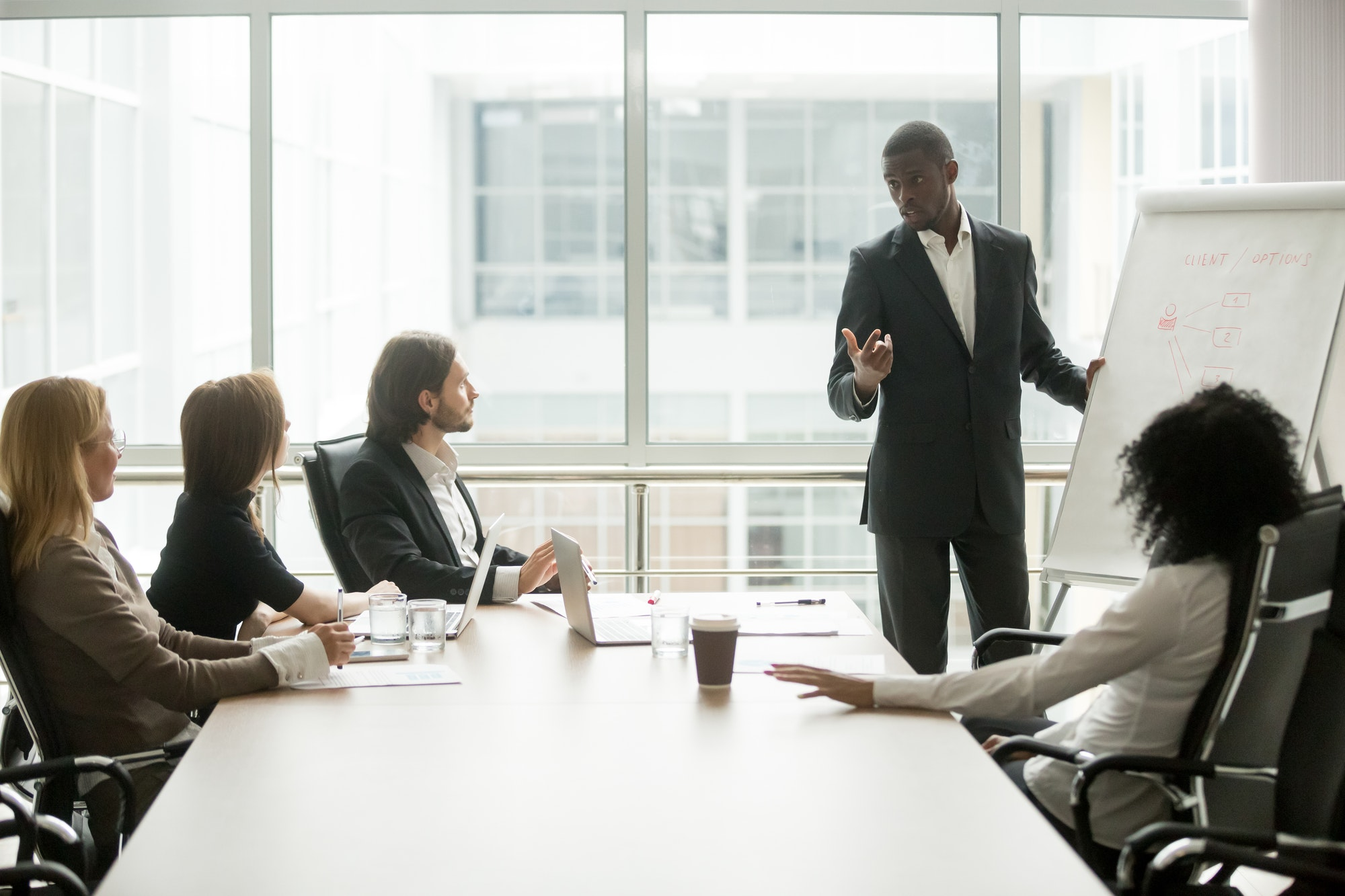 Black coach giving presentation to clients at conference meeting room