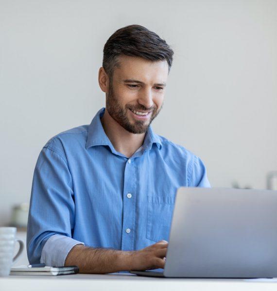 handsome-male-entrepreneur-working-on-laptop-at-desk-in-modern-office.jpg