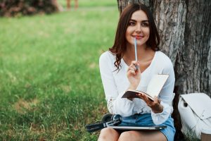 Writter thinks how to finish the chapter. Young woman have weekend and sits in the park at daytime